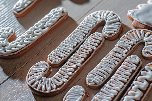 Biscuits en pain d'épice festifs faits à la main sous forme d'étoiles, de personnel, d'arbres de noël sur un comptoir léger.
