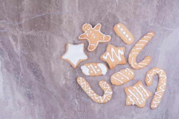 Biscuits de pain d'épice de forme de bâton, étoile et ovale sur le marbre