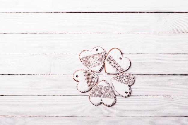 Biscuits de pain d'épice en forme de coeur avec du glaçage sur un fond en bois