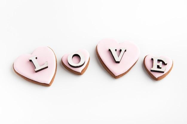 Biscuits de pain d'épice en forme de coeur avec glaçage au sucre rose sur une surface blanche et inscription love.