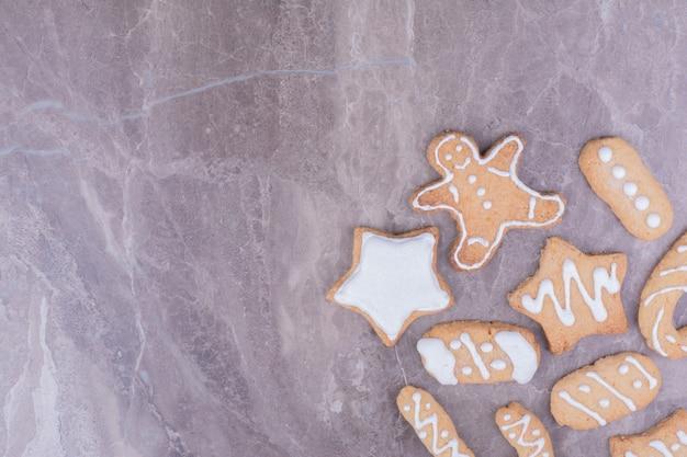 Biscuits en pain d'épice en forme d'étoile, de bâton et ovale sur marbre.