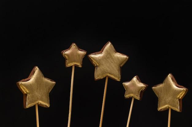 Biscuits de pain d'épice en forme d'étoile de couleur or sur un bâton sur fond noir