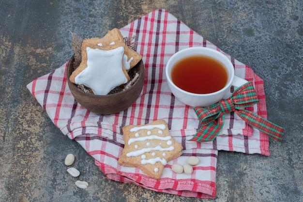 Biscuits en pain d'épice en forme d'étoile et tasse de thé sur la nappe. photo de haute qualité