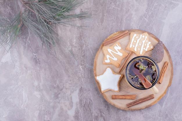 Biscuits en pain d'épice en forme d'étoile avec une tasse de tisane et de cannelle.