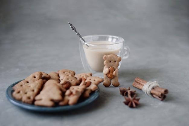 Biscuits de pain d'épice avec forme d'ours tenant des amandes avec des bâtons de cannelle et du lait de poule