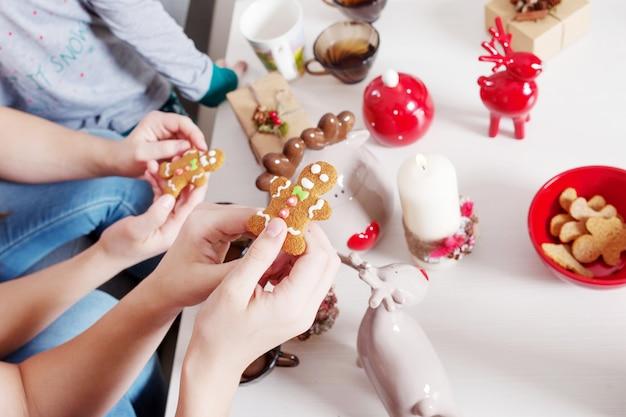 Biscuits de pain d'épice à la main pour noël dans les mains des enfants.