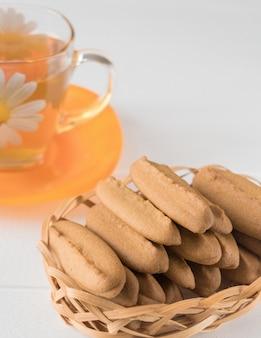 Biscuits de pain d'épice à la main sur une table en bois blanche.