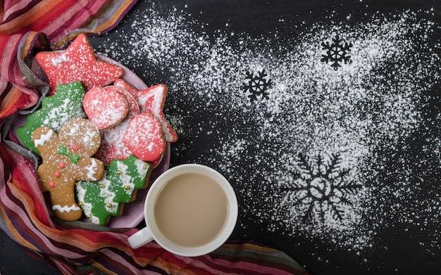 Biscuits en pain d'épice multicolores dans un bol et cacao dans une tasse sur un dessus noir