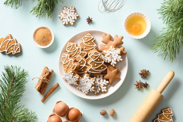 Biscuits de pain d'épice de noël sur bleu. joyeux noël et bonne année fond de cuisson. style plat.