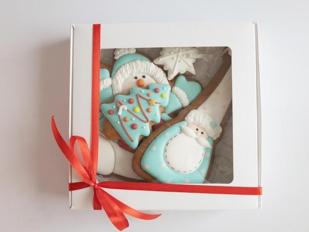 Biscuits de pain d'épice de noël glacés dans une boîte cadeau blanche avec ruban rouge