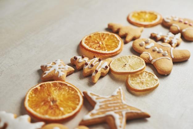 Biscuits de pain d'épice de noël et orange séchée et épices sur tableau blanc
