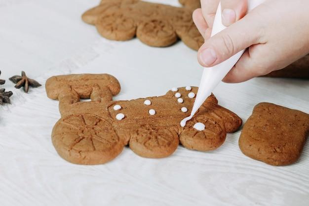 Biscuits de pain d'épice de noël peints avec du sucre glace. la fille de confiseur peint des biscuits