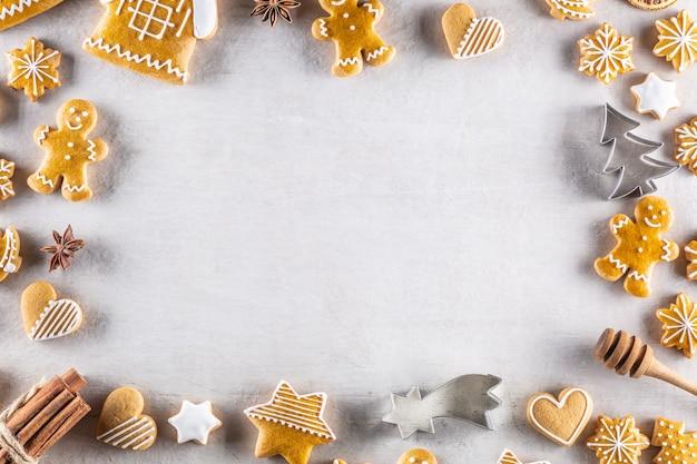 Des biscuits de pain d'épice de noël se trouvent sur la table avec de la cannelle et des pommes de pin - copiez l'espace.