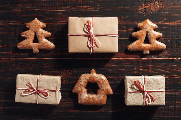 Biscuits de pain d'épice de noël sous la forme d'un arbre de noël et des cadeaux d'artisanat sur un bois.