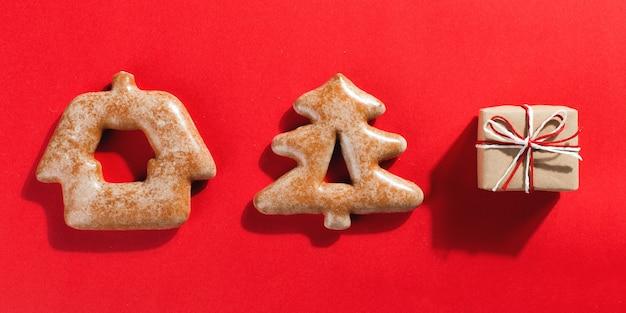 Biscuits de pain d'épice de noël sous la forme d'un arbre de noël et des cadeaux d'artisanat sur un fond rouge, surface.