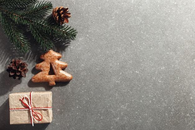 Biscuits de pain d'épice de noël sous la forme d'un arbre de noël et des cadeaux d'artisanat sur une pierre, surface.