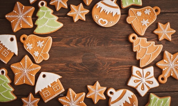Biscuits de pain d'épice de noël sous la forme d'une étoile se trouvent sur un fond en bois brun foncé.