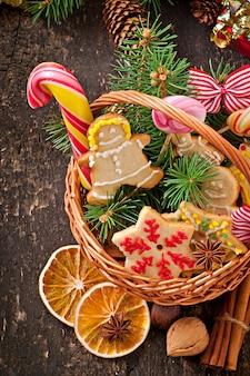 Biscuits de pain d'épice de noël et sucettes dans un panier sur fond de bois ancien