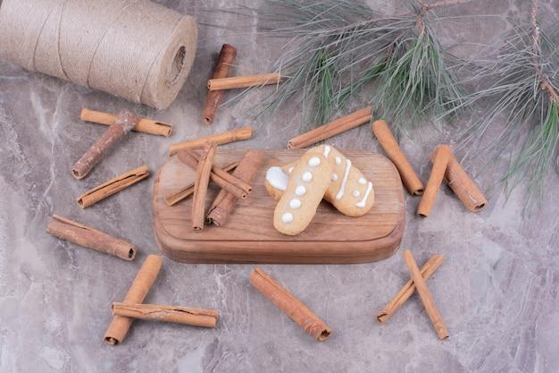 Biscuits en pain d'épice ovale avec des bâtons de cannelle autour de la pierre
