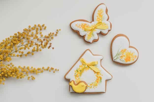 Biscuits de pain d'épice de pâques et fleurs de mimosa sur fond blanc. espace copie vue de dessus. concept de joyeuses pâques.
