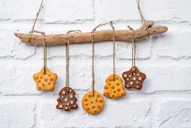 Biscuits de pain d'épice suspendus sur une corde sur un mur de briques blanches.