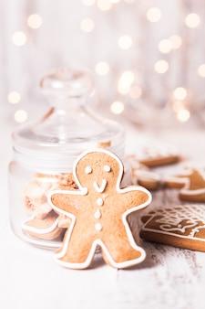Biscuits de pain d'épice sur une table et lumières de noël sur fond