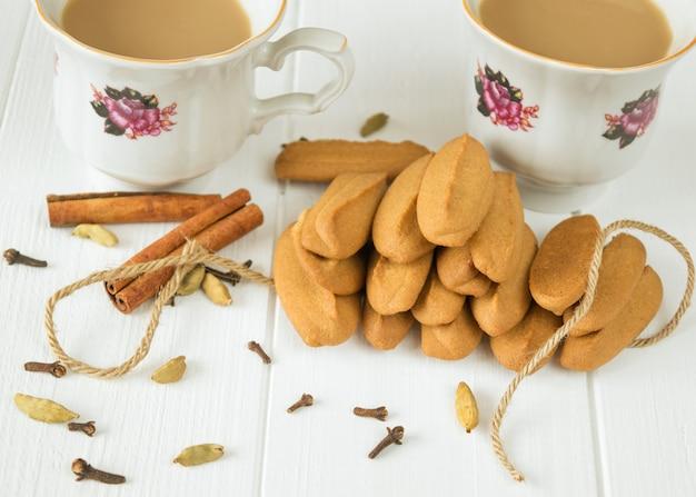 Biscuits de pain d'épice avec une tasse de café sur une table en bois blanche.