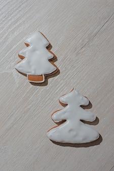 Biscuits en pain d'épices festifs faits à la main sous forme d'étoiles, de personnel, d'arbres de noël sur un comptoir léger.