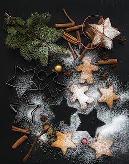 Biscuits de pain d'épices traditionnels de noël avec du sucre en poudre, de l'anis et des bâtons de cannelle sur fond noir