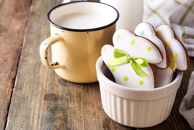 Biscuits de pâques en forme de lapin, faits à la main avec une tasse de lait.