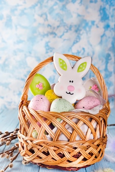 Biscuits de pâques, lapins et œufs dans un panier sur fond bleu clair