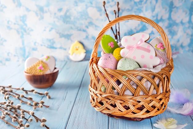 Biscuits de pâques, lapins et oeufs de pâques multicolores dans un panier sur fond bleu clair