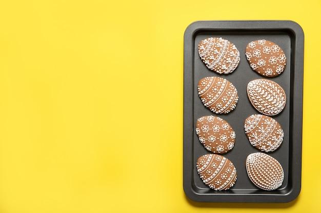 Biscuits de pâques sur une plaque à pâtisserie sur fond jaune. vue de dessus. œufs de pâques.