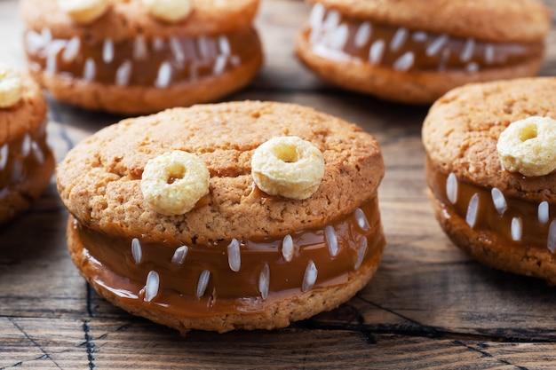 Biscuits à la pâte de crème en forme de monstres pour la fête d'halloween. visages faits maison drôles faits de biscuits à l'avoine et de lait concentré bouilli.