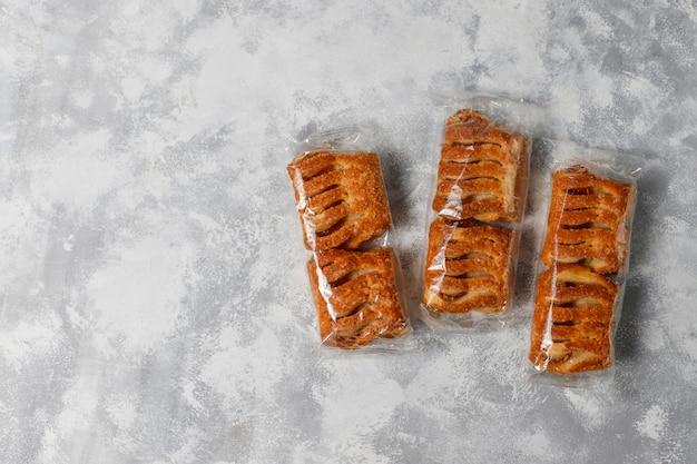 Biscuits de pâte feuilletée remplis de confiture de pommes et de pommes rouges fraîches sur du béton léger