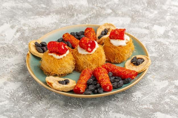 Biscuits pâtissiers de l'est à l'intérieur de la plaque verte avec des fruits secs à la crème blanche et peu de confitures