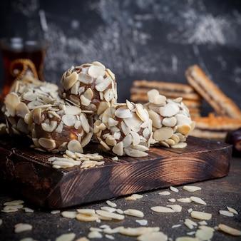 Biscuits pistache vue latérale sur bois et fond texturé noir.