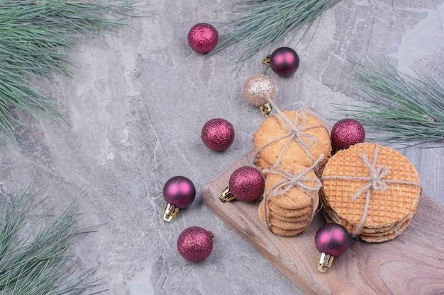 Biscuits sur une planche de bois avec des boules de noël paillettes rouges autour