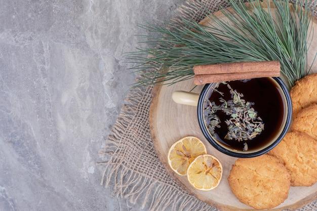 Biscuits sur une planche de bois avec une tasse de vin brillant