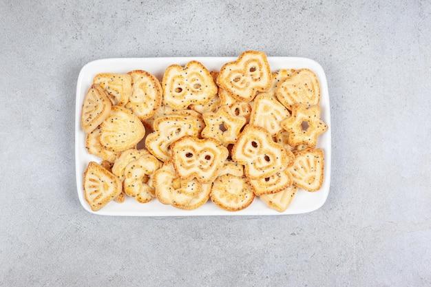 Biscuits sur une plaque blanche sur fond de marbre. photo de haute qualité