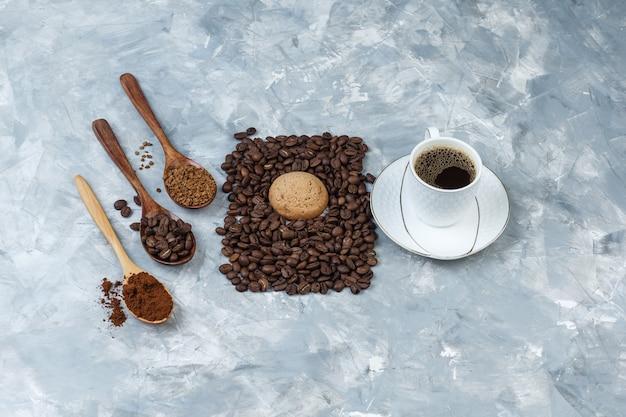Biscuits à plat, tasse de café avec des grains de café, café instantané, farine de café dans des cuillères en bois sur fond de marbre bleu clair. horizontal