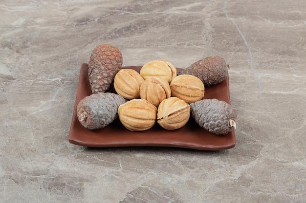 Biscuits et pommes de pin en forme de noix sur une plaque sombre.