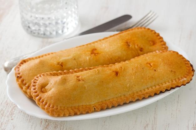 Biscuits portugais typiques sur une assiette et un verre d'eau