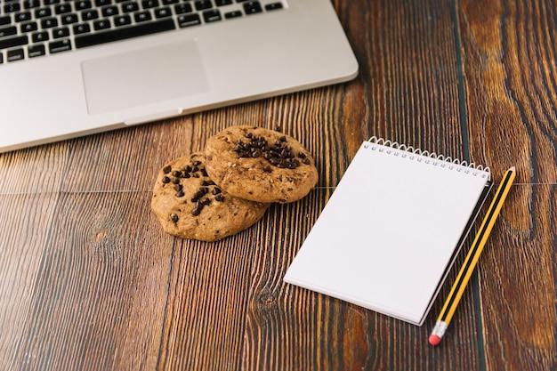 Biscuits près de cahier et ordinateur portable