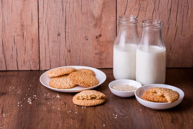 Biscuits ronds au sésame avec du lait et sur la table.