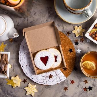 Biscuits ronds avec de la confiture en forme de coeur dans une boîte cadeau parmi les décorations de noël