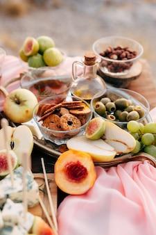 Biscuits ronds dans un bol sur une table avec des olives vertes une bouteille d'huile d'olive et de fruits