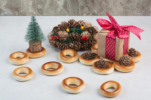 Biscuits ronds savoureux avec des pommes de pin et boîte-cadeau sur fond blanc. photo de haute qualité