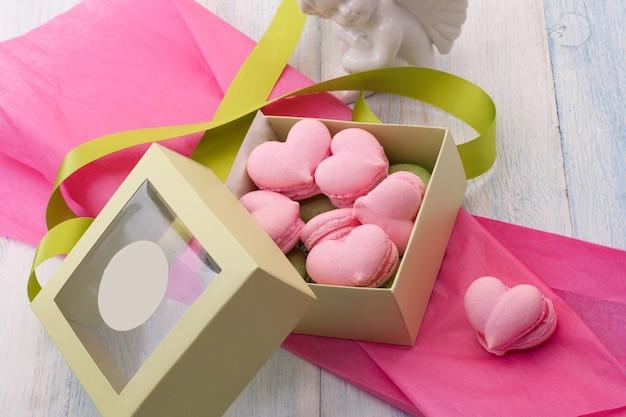 Biscuits roses en forme de coeur dans une boîte cadeau décorée de ruban et d'ange sur des planches de bois