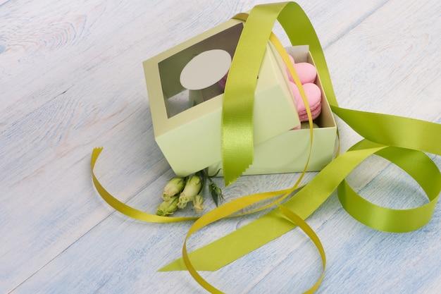 Biscuits roses en forme de coeur dans une boîte cadeau ornée de ruban et de fleurs